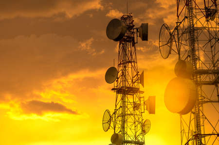 Telecommunication towers with wireless antennas on golden sky