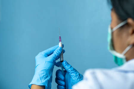 Doctor with gloves holding syringe and injectable contraceptive bottle preparing for injection Standard-Bild