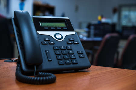 IP telephone device on wooden table in office room