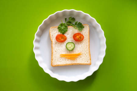 Fun food for kid, emotion face sandwich bread with vegetables white plate on green table