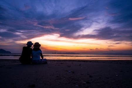 A couple enjoying honeymoon vacation on the beach at sunset time Standard-Bild