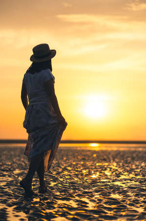 Lonely woman walking on sand beach at sunset time
