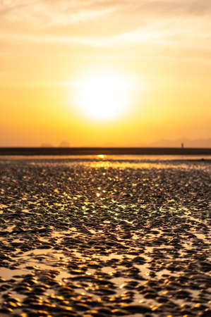 The scenery of the sea during sunset and patterns of sand in the low tide at golden sun light Фото со стока