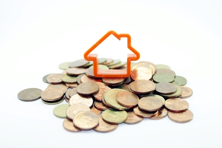 Mortgage concept by house on top laid with coins on white background