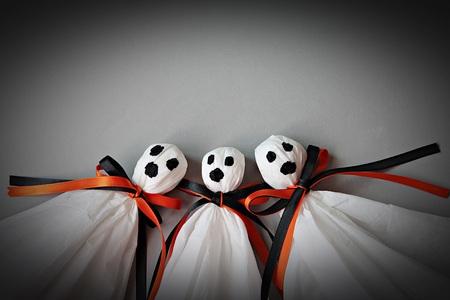 ハロウィーンの概念の背景: 黒、白いティッシュ ペーパーから作られた 3 つのハロウィーン幽霊 DIY と灰色の背景にオレンジ リボン