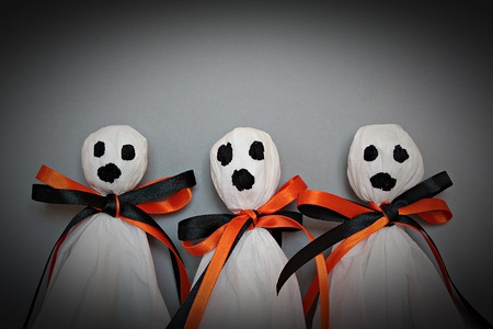Halloween concept background : Three halloween ghosts DIY made from white tissue paper, black and orange ribbon on gray background Stock Photo