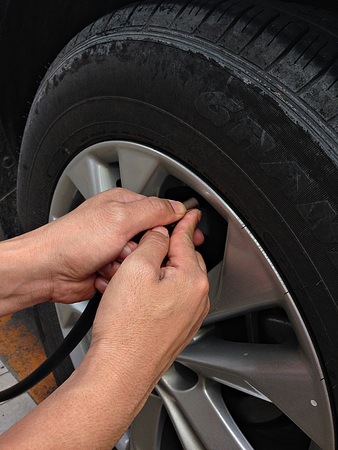 air pressure: Man filling air pressure in the tire of car, filling tire pressure Stock Photo