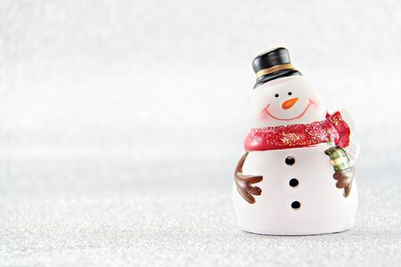 Merry Christmas or Happy New Year concept : Cute snowman doll on silver glitter paper background Stock Photo