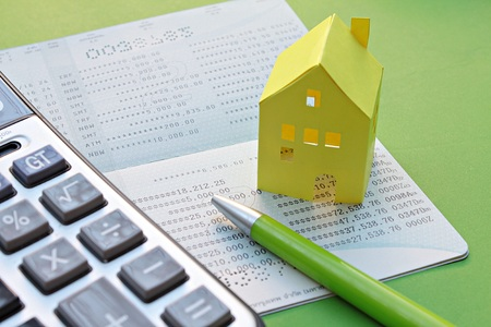 business savings: Business, finance or mortgage concept : Savings account passbook, calculator, pen and yellow paper house on green background