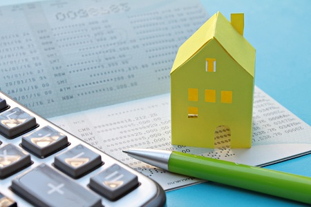 checking account: Business, finance or mortgage concept : Savings account passbook, calculator, pen and yellow paper house on blue background
