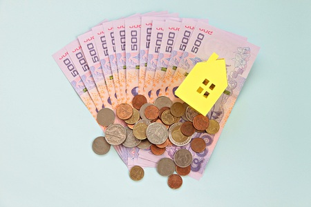 Business, mortgage or savings money concept : Thai money baht, coins and yellow paper house on blue background
