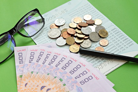 checking account: Business, finance or savings concept : Savings account passbook, Thai money baht, coins, glasses and pen on green background
