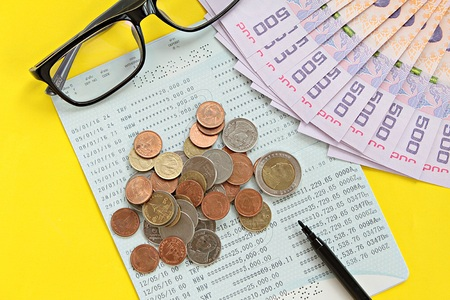checking account: Business, finance or savings concept : Savings account passbook, Thai money baht, coins, glasses and pen on yellow background