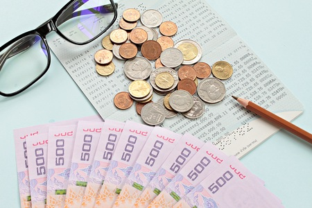 checking account: Business, finance or savings concept : Savings account passbook, Thai money baht, coins, glasses and pen on blue background