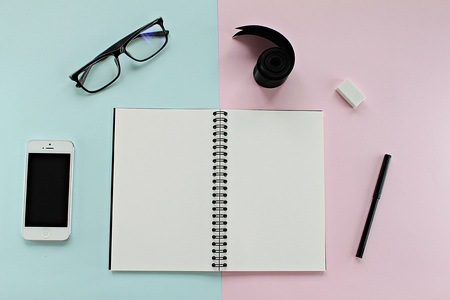 iphone5: CHONBURI, THAILAND - December 5, 2016 : Workspace desk with blank notebook, Iphone5, glasses and office stationery set on blue and pink background for business or work day Editorial