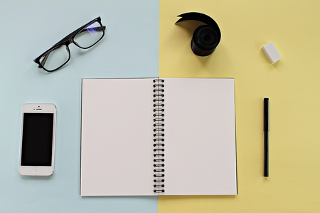 iphone5: CHONBURI, THAILAND - December 5, 2016 : Workspace desk with blank notebook, Iphone5, glasses and office stationery set on blue and yellow background for business or work day Editorial