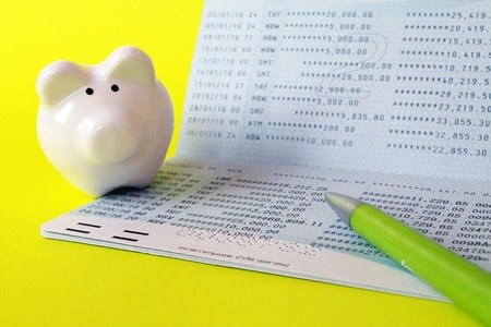 Business, finance, investment or savings money concept : Savings account passbook, piggy bank and pen on yellow background