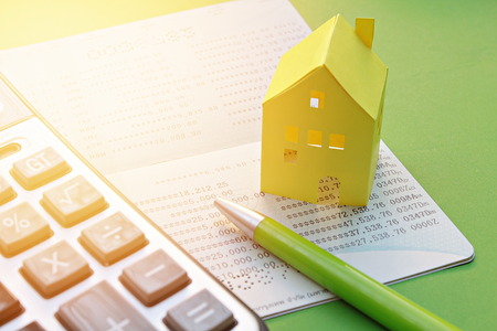 Business, finance savings or mortgage concept : Savings account passbook, calculator, pen and yellow paper house on green background