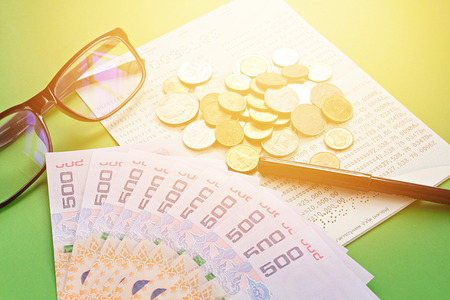 checking account: Business, finance, investment or savings concept : Savings account passbook, Thai money , coins, eye glasses and pen on green background