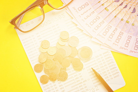 checking account: Business, finance, investment or savings concept : Savings account passbook, Thai money, coins, eye glasses and pen on yellow background