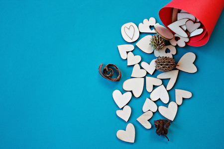 heartfelt: Valentines day or love concept : Wooden hearts in a red craft paper cornet on blue background