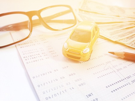 Business, finance, savings, banking or car loan concept : Miniature car model, pencil, eyeglasses, money and savings account passbook or financial statement on white background Stock Photo