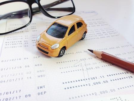 ビジネス、金融、貯蓄、銀行、車ローンの概念: 小型車モデル、鉛筆、眼鏡、普通預金通帳または白い背景に財務諸表