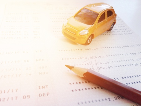 Business, finance, savings, banking or car loan concept : Miniature car model, pencil and savings account passbook or financial statement on white background Stock Photo