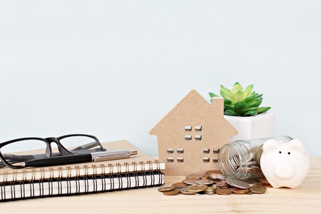 Business, finance, savings, property ladder, mortgage or loan concept : Wood house model, piggy bank, coins scattered from glass jar, notebooks, pen and eyeglasses on wooden background