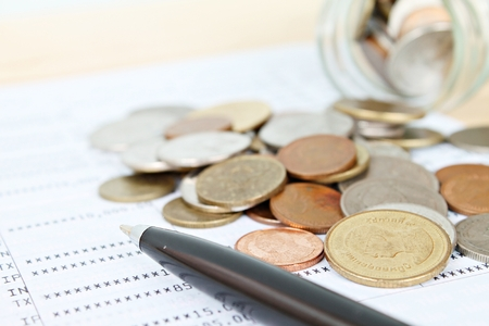 Business, finance, savings or loan concept : Coins scattered from glass jar and pen on saving account passbook or financial statement