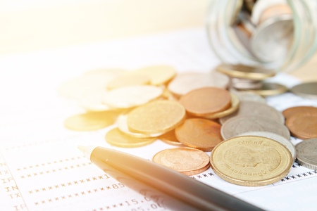 Business, finance, saving money, banking, loan, investment, taxes or accounting concept : Coins scattered from glass jar and pen on saving account book or financial statement Stock Photo