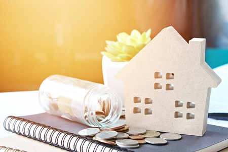 Business, finance, savings, property ladder, mortgage or loan concept : Wood house model and coins scattered from glass jar on notebook paper Standard-Bild