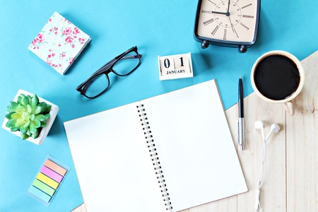 Business, weekend, holiday or new year planning concept : Top view or flat lay of open notebook paper, accessories, cube calendar and coffee cup on wooden background, ready for adding or mock up Archivio Fotografico