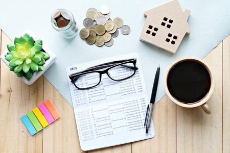 Affaires, finances, épargne, échelle de la propriété, concept de prêt hypothécaire: Vue de dessus ou plat jeter du livret de compte d'épargne ou état financier, modèle de maison en bois et accessoires sur fond en bois