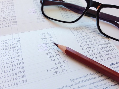 Business, finance, saving money, banking, loan, investment, taxes or accounting concept : Pen and eyeglasses on saving account book or financial statement 写真素材