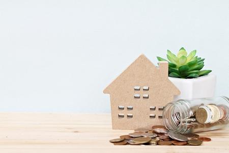 ビジネス、金融、貯蓄、不動産のはしごや住宅ローンの概念: 木製の家モデル、机のテーブルの上にガラスの瓶から散乱コイン