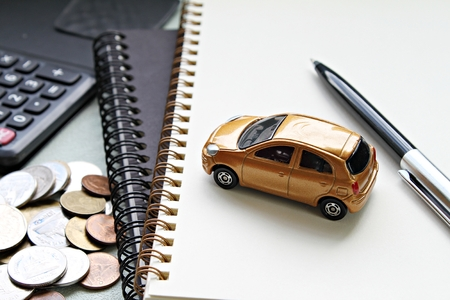 Business, finance, saving money, banking or car loan concept : Miniature car model, pen, notebook papers, calculator and coins on office table