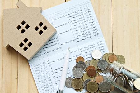 ビジネス、金融、貯蓄、不動産ローンや住宅ローンの概念: トップビューまたは木製の家モデルのフラットなレイアウト、オフィスデスクのテーブル