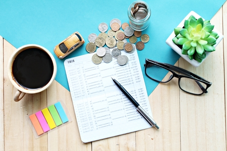 Business, finance, saving money or car loan concept :  Top view or flat lay of miniature car model, saving account book or financial statement and coins on office desk table