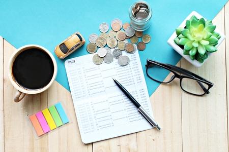 Geschäft, Finanzierung, einsparendes Geld- oder Autokreditkonzept: Draufsicht oder flache Lage des Miniaturautomodells, Sparkontobuch oder Bilanz und Münzen auf Schreibtischtisch Standard-Bild - 90767192