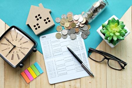 Affaires, finance, épargne, concept immobilier ou hypothèque: vue de dessus ou pose à plat du modèle de maison en bois, livre de comptes épargne ou relevé financier et pièces de monnaie sur la table de bureau Banque d'images