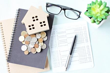 ビジネス、金融、節約では、不動産融資や住宅ローンの概念: 木の家モデル、オフィス デスク テーブルの帳簿や財務諸表のコインを保存の平面図ま