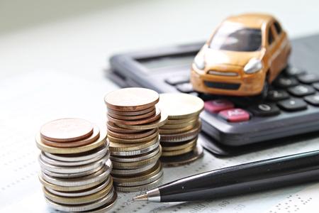 ビジネス、金融、お金や車のローンの概念を保存: 小型車モデル、コイン スタック、電卓、オフィス デスク テーブルの帳簿や財務諸表を保存