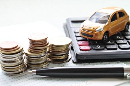 Geschäfts-, Finanz-, Spargeld- oder Autokreditkonzept: Miniaturautomodell, Münzenstapel, Taschenrechner und Sparkontobuch oder Finanzbericht auf Schreibtischtabelle Standard-Bild - 88762389