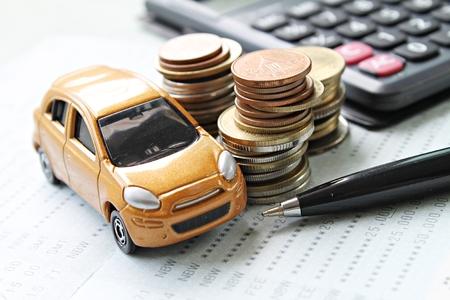 Zaken, financiën, geld besparen of autolening concept: Miniatuur automodel, muntenstapel, rekenmachine en spaarrekeningboek of financieel overzicht op bureaulijst Stockfoto