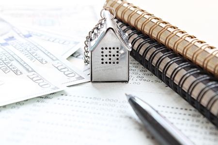 Business, finance, saving money, property ladder or mortgage loan concept : House model, American Dollar cash money, notebook and savings account passbook or financial statement on office desk table