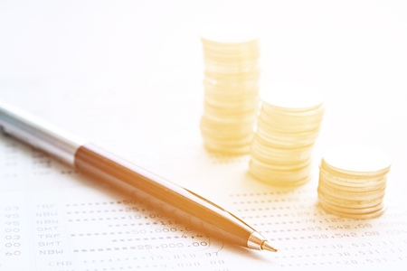 Business, finance, saving money or investment concept : Coin stacks, pen and savings account passbook or financial statement on office desk table