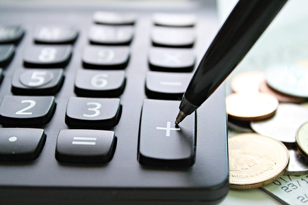 Business, finance, saving money, banking, loan, investment, taxes or accounting concept : Pen press on plus button calculator and coins on office desk table Archivio Fotografico