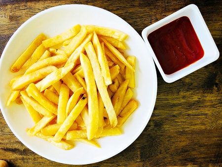 Food concept : Top view of tasty  french fries or potato fries with ketchup on wooden table