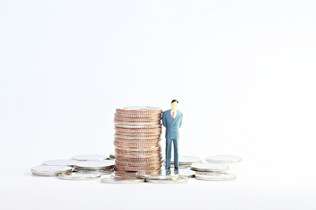 Business success, finance, leadership or money management concept : Miniature business man model and coins on white background Archivio Fotografico